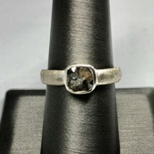 square oval gemstone with pearlescent band on black stand